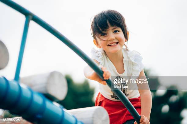 Cute 3 year old mixed race girl having fun at playground