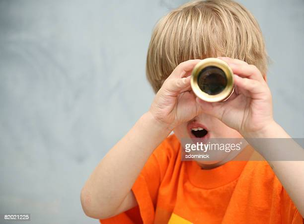 A cute 4 1/2 year old boy looking though a telescope with a surprised expression.