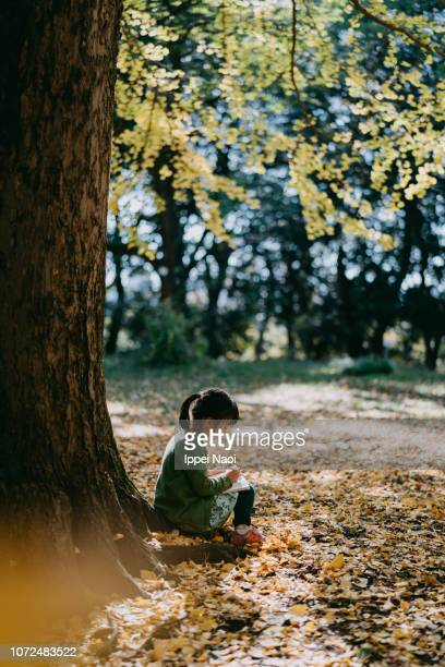 Cute 4 year old girl sitting under tree with book in autumn