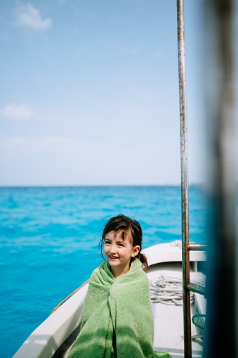 Cute 4 year old girl wrapped in towel, sitting on boat with blue tropical sea - gettyimageskorea