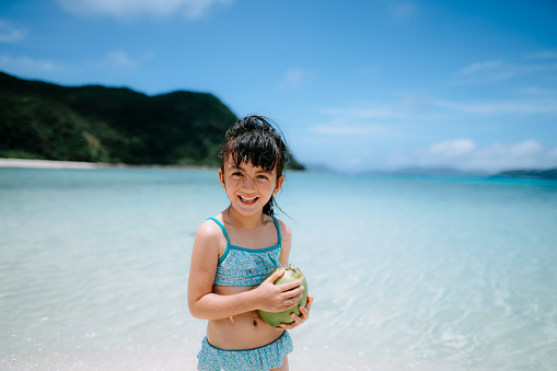 Cute 5 year old girl with coconut on tropical beach, Okinawa, Japan - gettyimageskorea