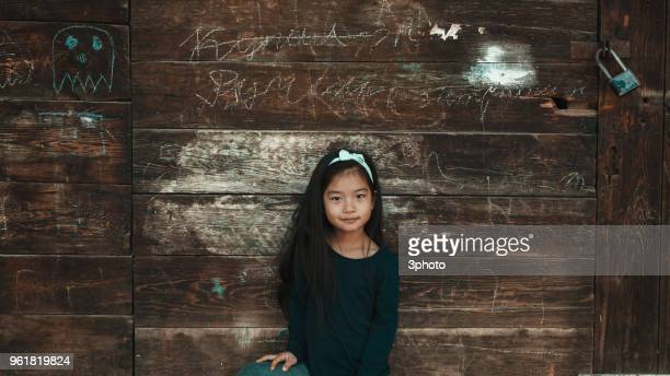 cute 5-6 years girl standing against the old wooden wall - 4 5 years stock pictures, royalty-free photos & images