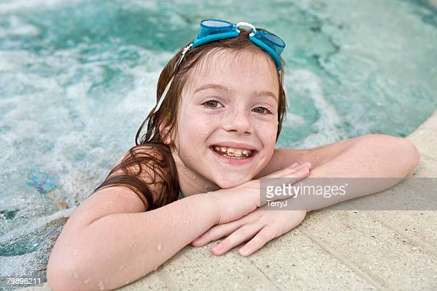 Cute 8 year old girl in a whirlpool with swim goggles.