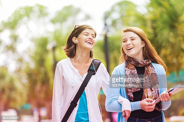 Cute adolescent girls walking to bus stop before school