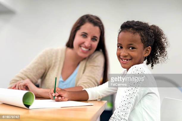 Cute African American girl doing a writing exercise for rehab