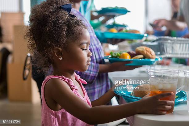 Cute African American girl receives meal at soup kitchen