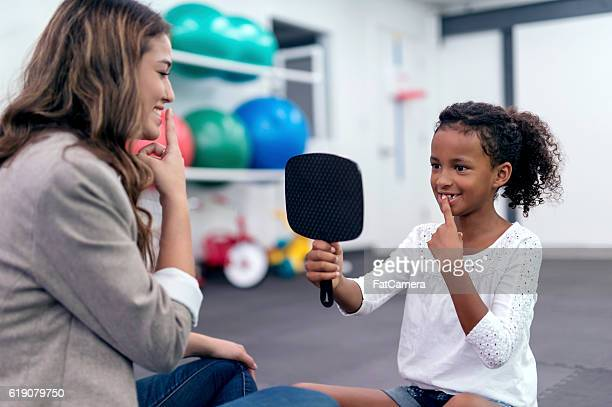 Cute African American girl using a mirror for speech therapy
