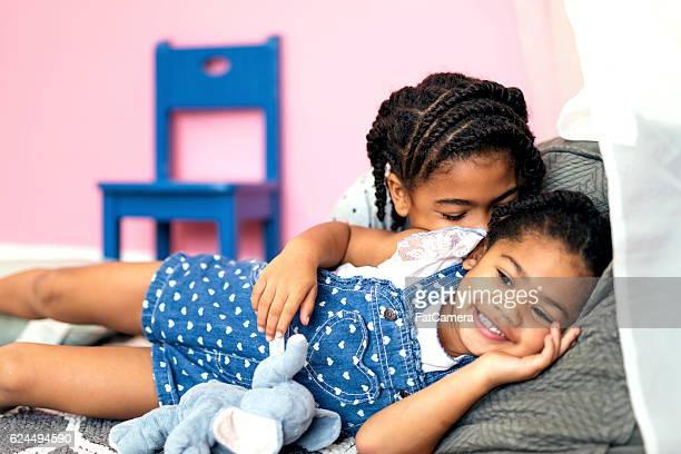 Cute African American girls relaxing together on the floor