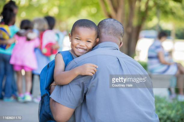 cute african american little boy hugs his dad before first day of preschool - first day of school stock pictures, royalty-free photos & images