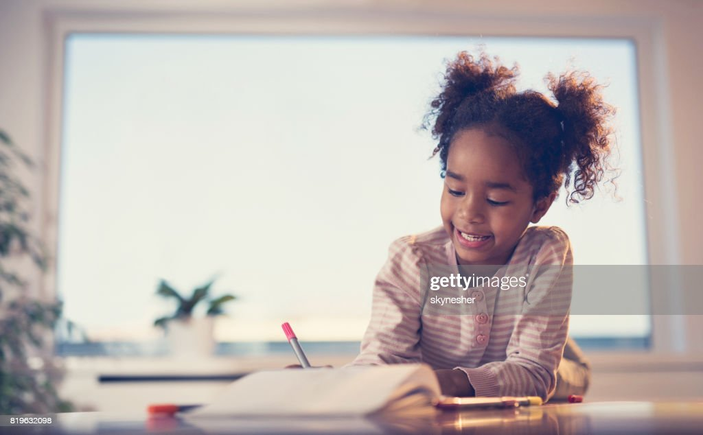 Cute African American little girl drawing on a piece of paper at home. : Stock Photo