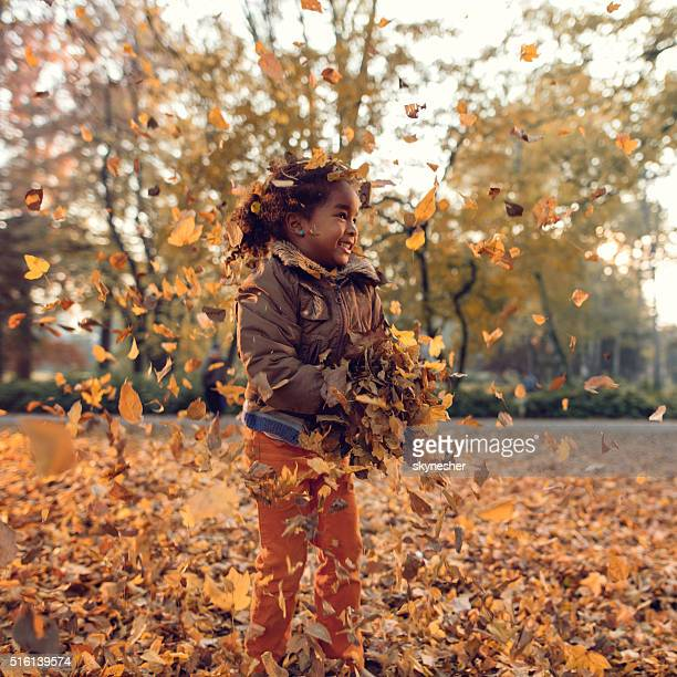 Cute African American little girl playing with autumn leaves.