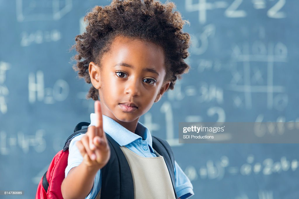 Cute African American private school child holding up one finger : Stock Photo
