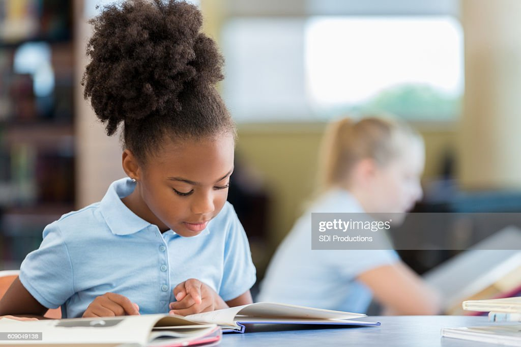 Cute African American schoolgirl reading a book in the library : Stock Photo