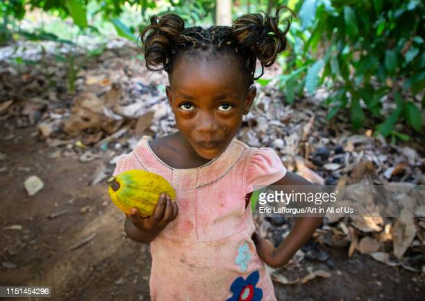 Cute african girl with a cocoa fruit pod in her hands, Région des Lacs, Yamoussoukro, Ivory Coast on May 7, 2019 in Yamoussoukro, Ivory Coast.