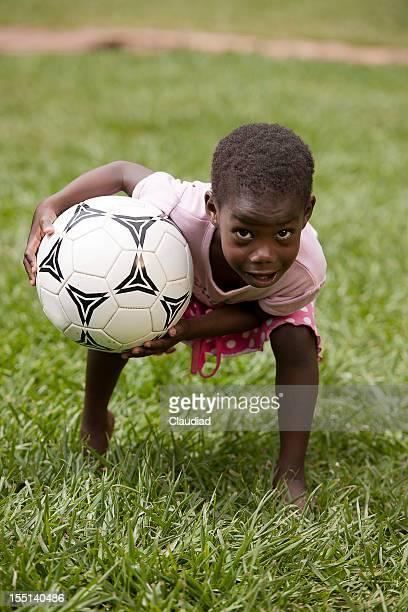 Jolie jeune fille africaine avec un ballon de football