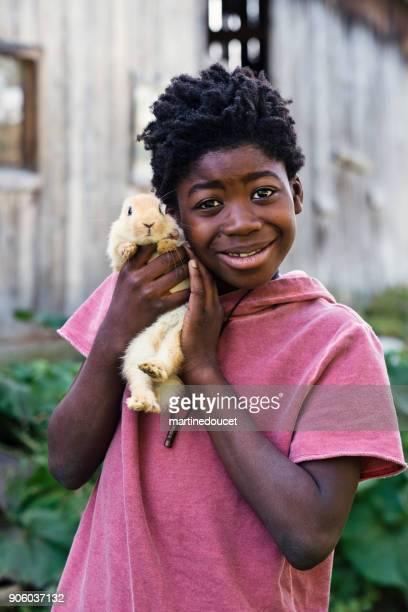 """söt afroamerikansk pojke hålla en baby kanin utomhus under våren. - """"martine doucet"""" or martinedoucet bildbanksfoton och bilder"""