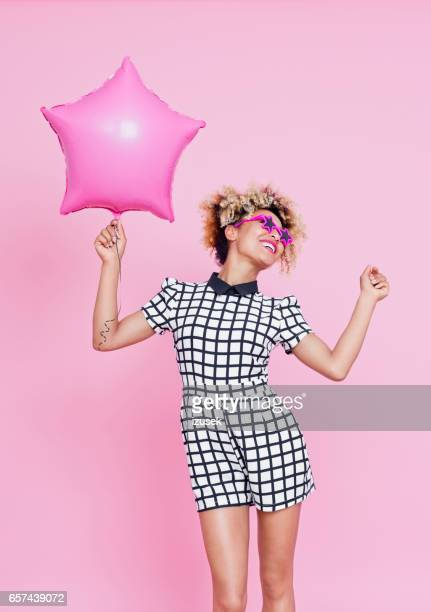 Cute afro american woman holding pink balloon