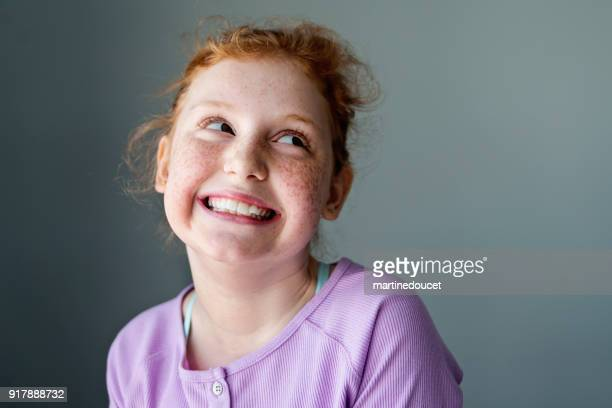 Cute and expressive preteen girl with redhead portrait.