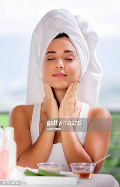 Mignonne et joyeux hispanique jeune femme appliquant aloe vera crème hydratante sur son visage.