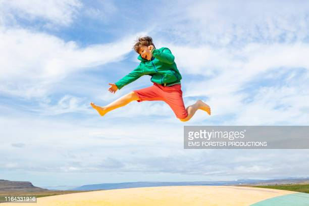 cute and young boy is bouncing off an air trampoline - play off stock pictures, royalty-free photos & images