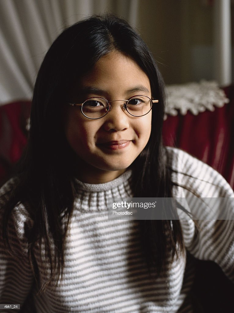 A cute asian american girl smiles shyly in a comfortable chair : Stockfoto