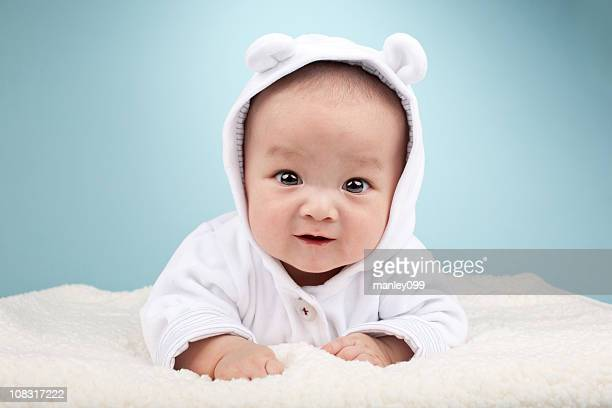 cute asian baby laying on stomach
