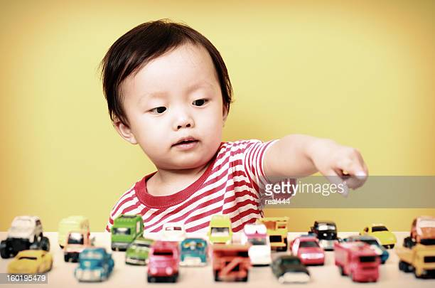 Cute Asian baby playing with car