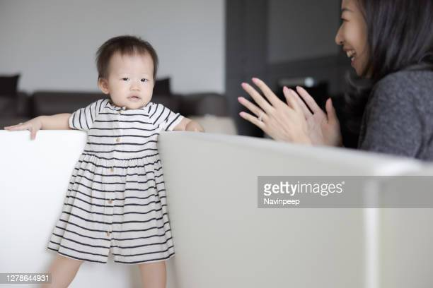 cute asian baby standing with her back in a corner of the playpen, mother cheering nearby - clapping hands stock pictures, royalty-free photos & images