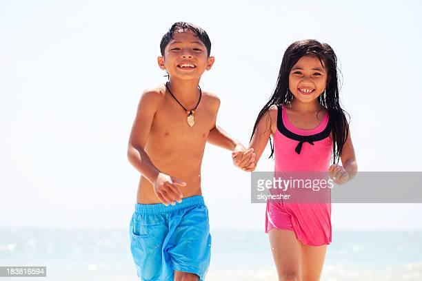 Süße asiatische Kinder Laufen am Strand.
