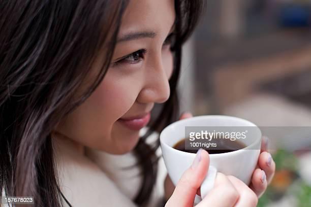 かわいいアジア人の女性がコーヒーを飲む