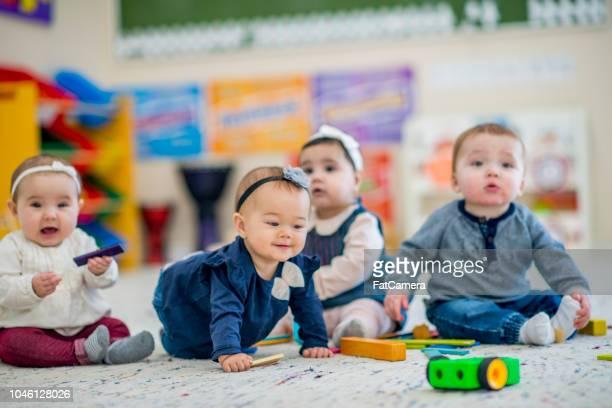 schattig baby's spelen met speelgoed in kinderdagverblijf - peuter stockfoto's en -beelden