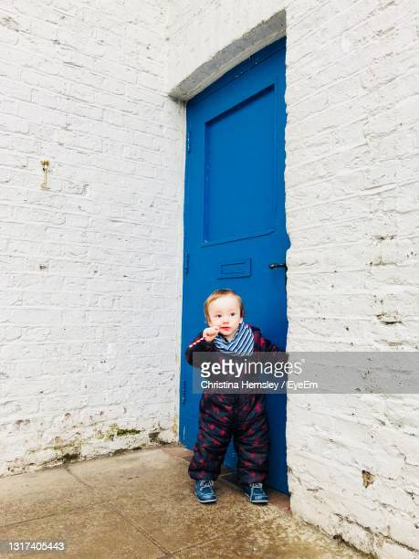 cute baby boy, barely a toddler, standing alone outside a blue wooden front door chewing a straw - one baby boy only stock pictures, royalty-free photos & images