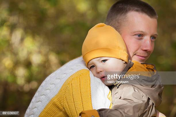 Cute baby boy being carried by thoughtful father at park during autumn
