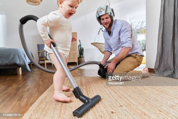 cute baby boy cleaning carpet with vacuum cleaner by father in living room at home - babyhood stock pictures, royalty-free photos & images