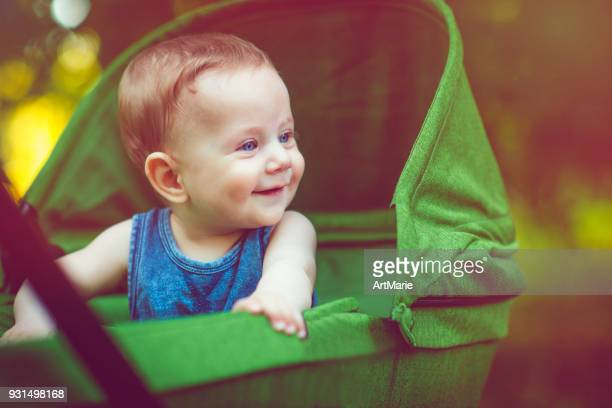 cute baby boy in carriage outdoors in summer - carriage stock pictures, royalty-free photos & images