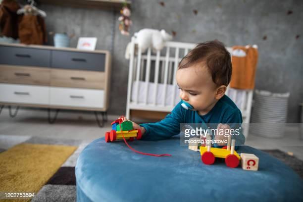 木製の列車で遊んでいるワンシーでかわいい男の子 - 模型の汽車 ストックフォトと画像