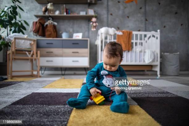 木製の列車で遊ぶパジャマのかわいい男の子 - 模型の汽車 ストックフォトと画像