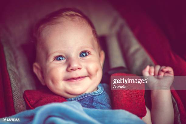 Cute baby boy in stroller smiling