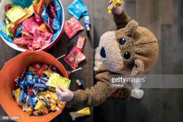 cute baby boy inside bear costume eating or grabbing candies - happy halloween stock photos and pictures