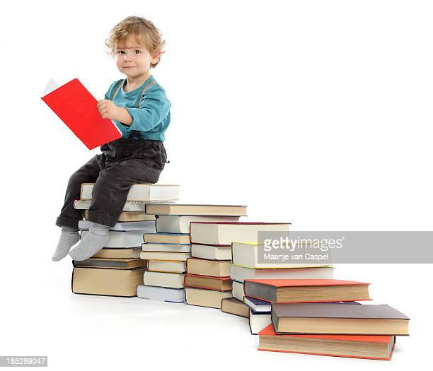 Cute baby Boy sitting on a Book Staircase