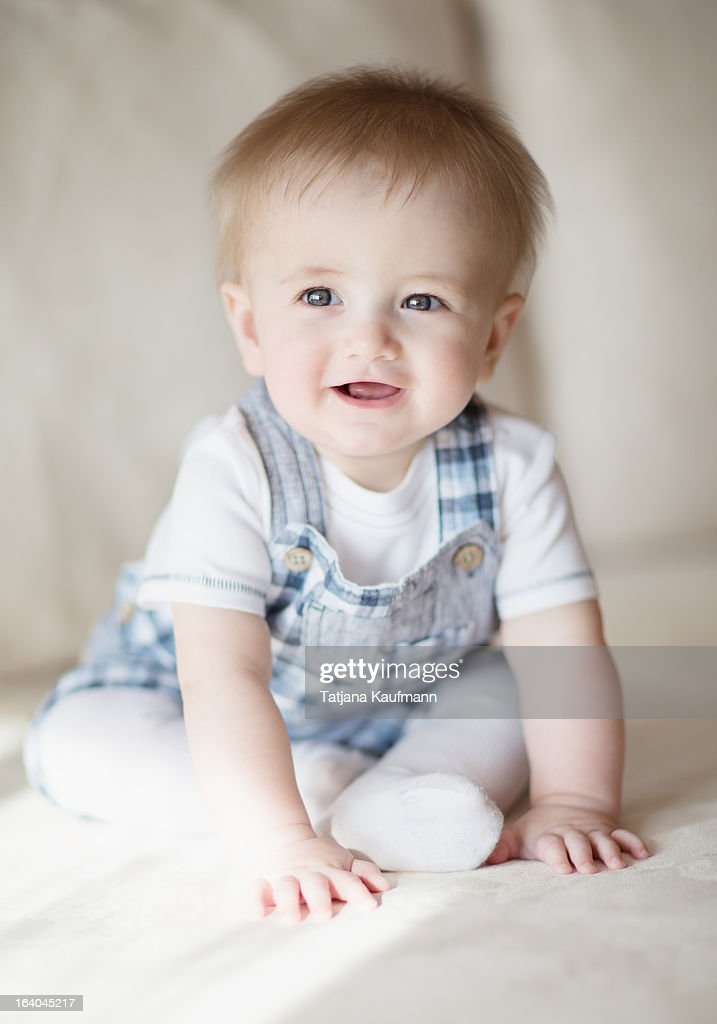 Cute Baby Boy sitting on a Sofa, laughing : Stock Photo