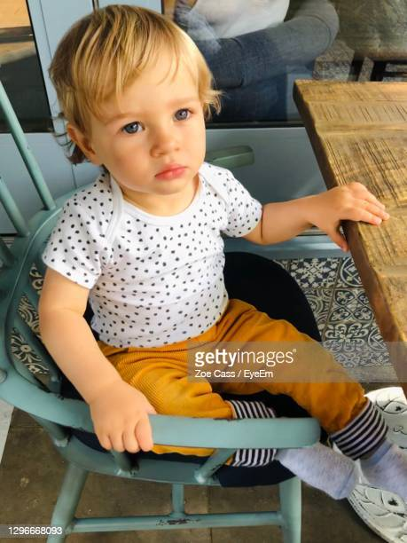 cute baby boy sitting on chair in restaurant - babyhood stock pictures, royalty-free photos & images