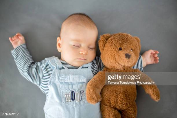 Cute baby boy, sleeping with teddy bear toy in a sunny living room, lying down on the sofa