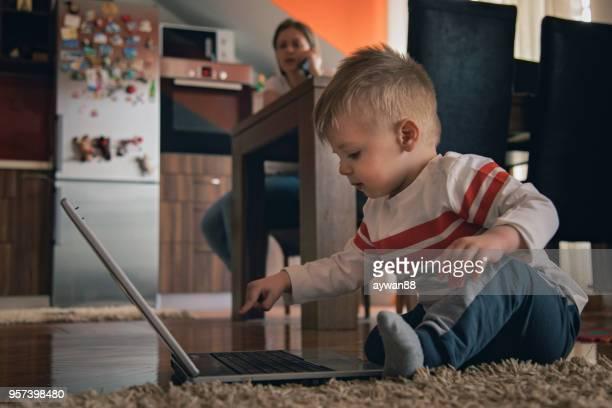 Cute baby boy using laptop computer