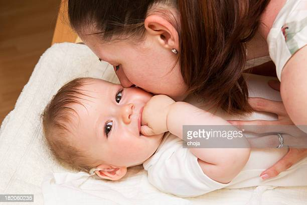 Cute baby boy wearing hearing aid with his mother