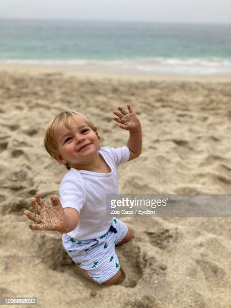 cute baby boy with messy hands kneeling at beach - babyhood stock pictures, royalty-free photos & images