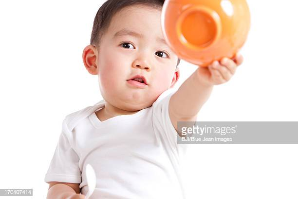 Cute baby boy with spoon and bowl