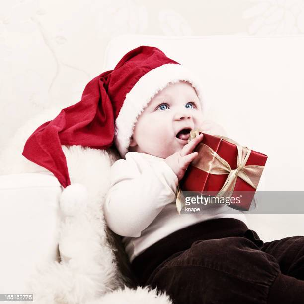 Cute baby concentrating on christmas gift