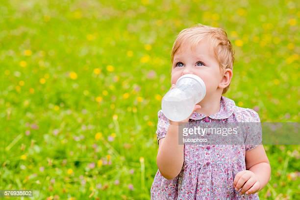 Cute baby drinking water from  bottle outside
