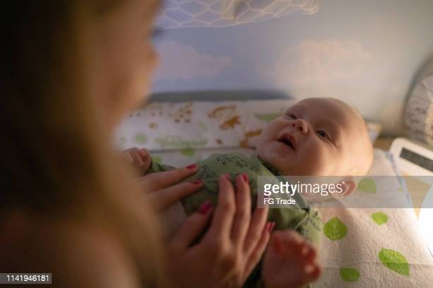 cute baby getting his diapers changed - mum changing nappy stock pictures, royalty-free photos & images